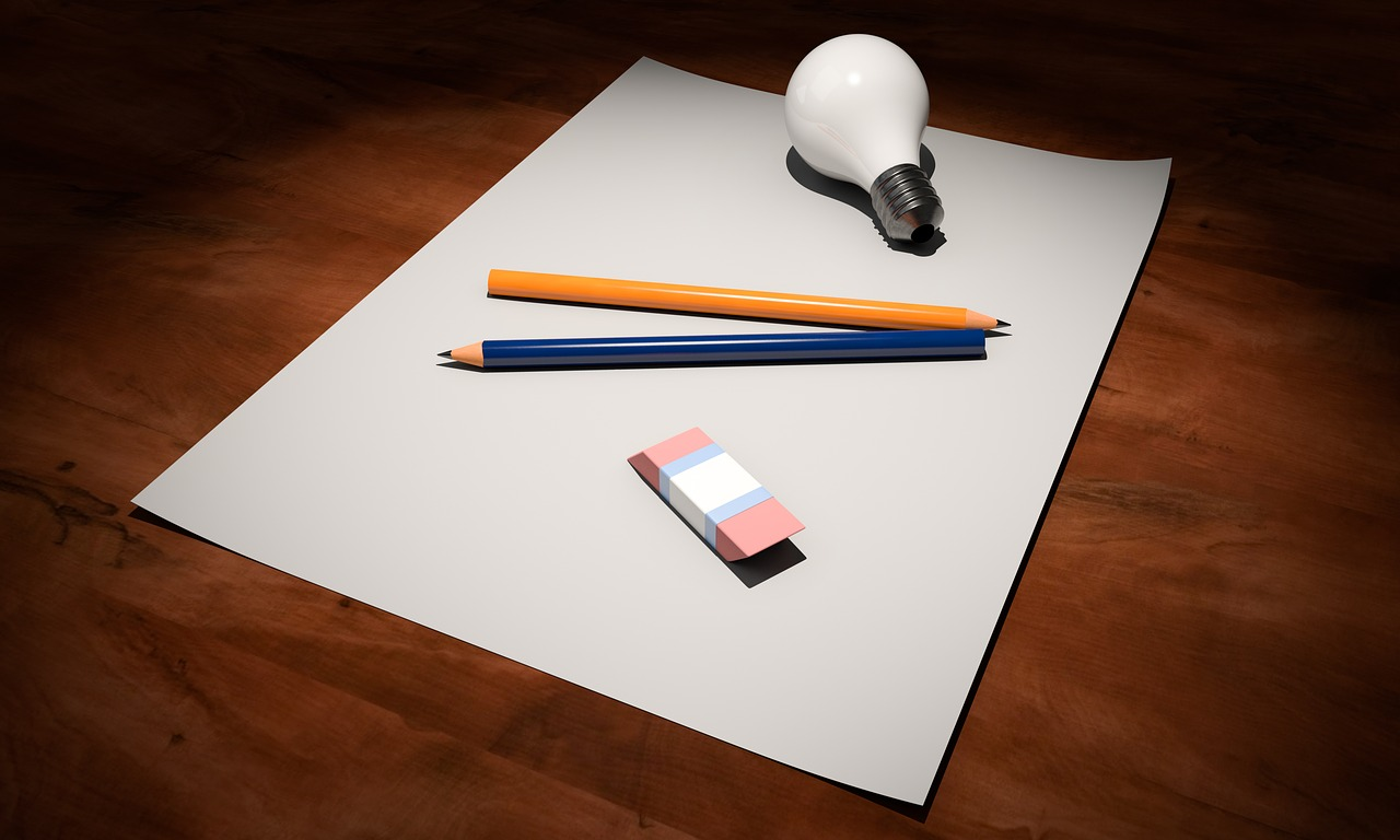 Creativity: A lightbulb, two pencils and an eraser on a blank page