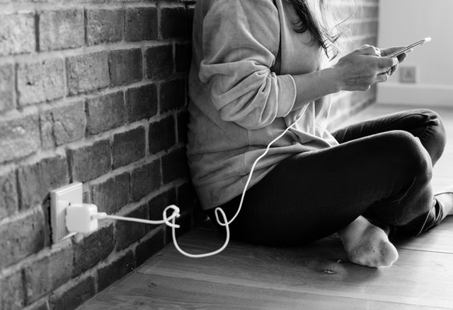 https://www.pexels.com/photo/grayscale-photography-of-person-using-smartphone-while-charging-1308749/